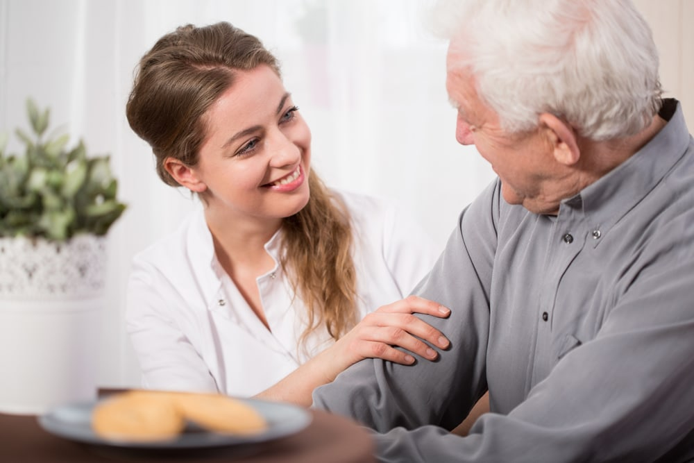 Aide with male patient in home smiling