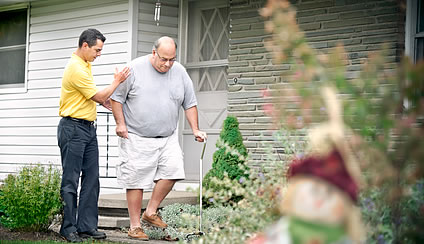 Male caregiver helping patient outside