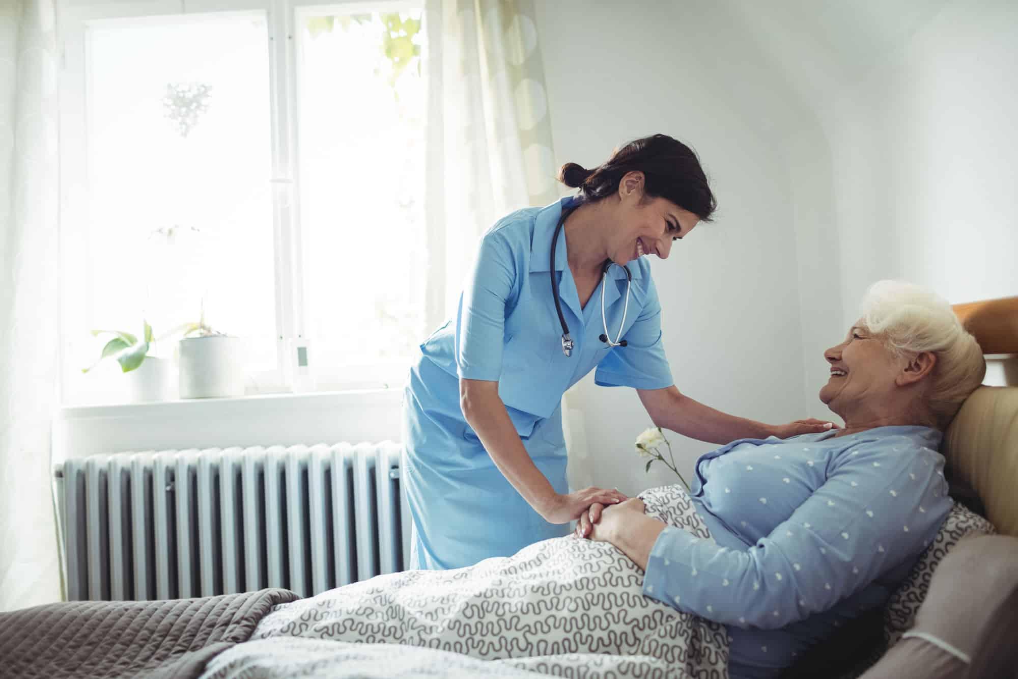 nurse providing care to bedridden patient